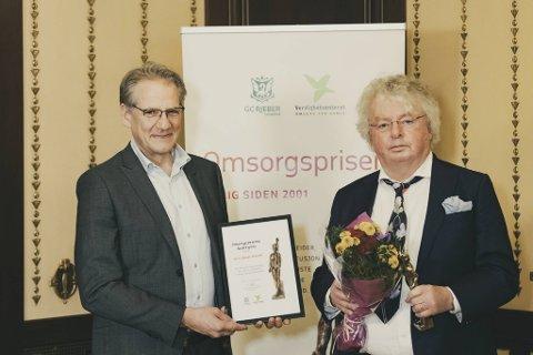 (Fra v.) Juryleder Sebastian von Hofacker fra Verdighetsenteret tildeler lege Stein B. Husebø hederstegnet for sitt mangeårig arbeid for samfunnets svakeste.