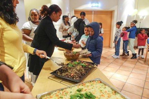 Mbrak Beyene Haylu (i midten) serverer etiopisk injerra-middag til Naod (8) og øvrige gjester på Nøstet. Rahel Darge (til v.) og Mehalet Worku er kokker.