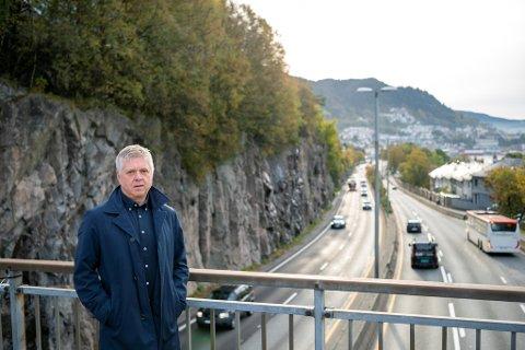 Trafikkplanlegger Helge Hopen ved veien som vil gå i en forlenget Fløyfjellstunnel, om ikke bybaneplanene ryker.