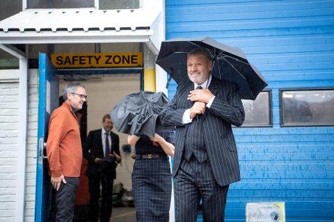 Industrimilliardær Anthony Langley måtte frem med paraplyen da han skulle besøke sin nye motorfabrikk i Åsane. Bergen Engines-klubbleder Idar Bruvik til venstre.