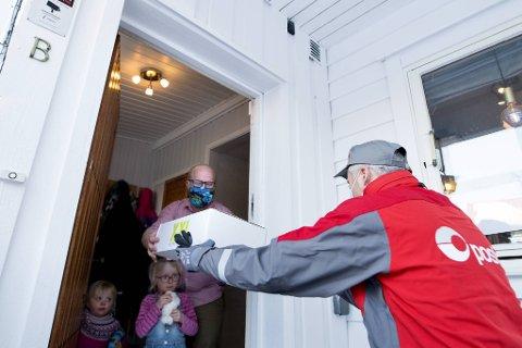 Bring-sjåfør Petter Nilsen (til h.) ringer på til XXL-kunde Lasse Kolbjørn Anke Hansen på Årstad og overleverer den forhåndsbestilte varen. Døtrene Hedvig (3) og Sonja (5) står i døråpningen.