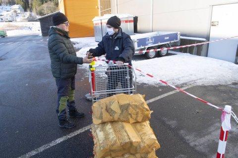 Obs Bygg-medarbeider Christoffer Johansen (til h.) kommer trillende ut porten med vedsekkene til kunde Svein Olav Eikner fra Fana som står klar med digital kvittering.