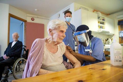 Sykepleier Aneb Hossain setter vaksinen på Synnøve Bernstrøm (92). Ektemann Egon (92) og sykepleierstudent Terje Bertheussen Brurås følger med.