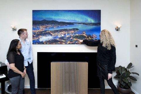 (Fra v.) Sorayda og Tom Arne Furnes har akkurat fått hjelp av kunstner Marianne Skjelbred å henge opp bestillingsverket hjemme i sin egen stue. Her studerer de noen av de delikate detaljene.
