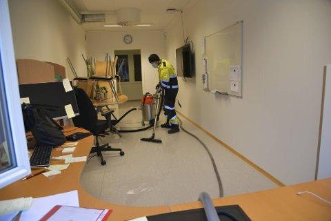 Brannmannskaper i fred med å tømme lokalene for vann.