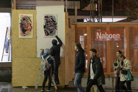 Her henger gatekunstneren E.B. opp de to maleriene sine utenfor Sundt.