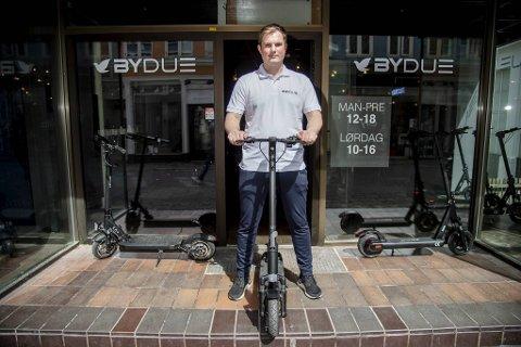 El-løperhjulselger Arnt Erik Hovda (22) foran den nyåpnede butikken i gågaten. Butikksjefen er fire år yngre enn ham, noe som sikkert forteller en hel del om kundegruppen.