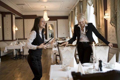 Markedsansvarlig ved Fleischers Hotel på Voss, Alette Hjelmeland (t.h) sier hele organisasjonen står samlet for å sikre driften ved hotellet. Servitør Linda Erkena gleder seg til å ta imot gjester igjen.