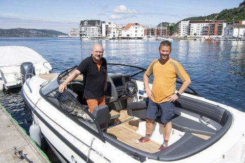 Båtselger Fredrik Soltvedt (til v.) i Sandviken overleverer en splitter ny daycruiser til Kjetil Bøe, som har ventet på godbiten siden januar. Rekordmange ønsker å kjøpe seg feriebåt og hytte ved sjøen i år.