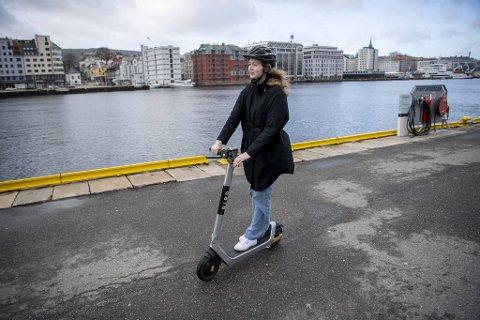 Med ti kroner i oppstartsavgift og tre kroner minuttet blir det fort dyrt når man skal leie el-løperhjul. Emma Fondenes Øvrebø, som her cruiser over Bryggen, anbefaler å kjøpe månedspass.