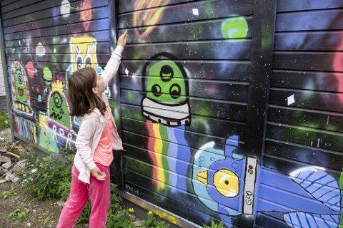 Serina Eriksen (10) viser frem den forrige veggen hun var med å dekorere. – Denne uken skal vi male veggen ved siden av her.