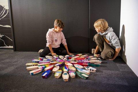 Bergenske skoleelever bidrar til forskningstoktet i Arktis. Her studerer Alfred (10) og Filip (10) båtene som andre barn og unge har dekorert.