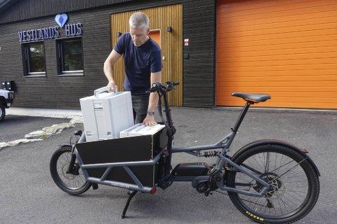 Møbelsnekker Tore Beinnes plasserer to svære verktøykasser på sitt selvbygde lasteplan. Siden i fjor har han halvert bilkjøringen til fordel for el-lastesykkelen han kjøpte med støtte fra Bergen kommune.