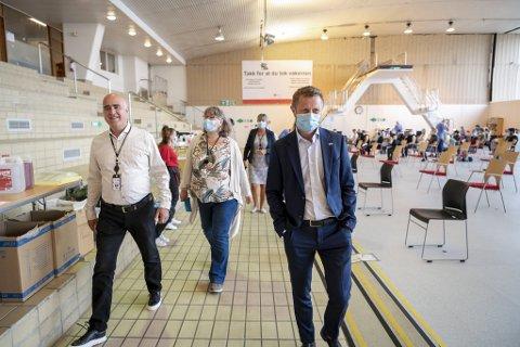 Helseminister Bent Høie (t.h.) med diriftsleder for vaksinestasjonene Hossein Therani og leder for vaksineprtosjektet Elisabeth Engelsen i Sentralbadet fredag.