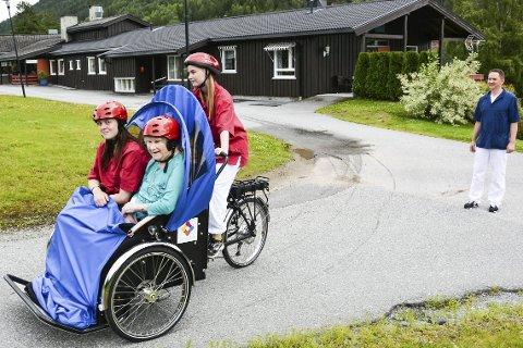 TESTKJØRING: Trivselsassistentene Nora Klev - som er sjåfør - og Malin Træen Kittilsen har tatt med en smått skeptisk Solveig Løvlid på en prøvetur med den nye el-sykkelen på Kryllingheimen. Alle kom helskinnet fra turen, som ble overvåket av fagleder Geir Haukeland.
