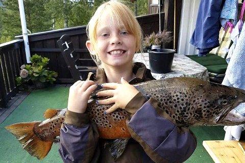 INGEN FISKESKRØNE: Josefine Stokke skal begynne i 3. klasse og vil nok fortelle om kjempeørreten. Her er beviset for at det ikke er en fiskeskrøne. Foto: Privat