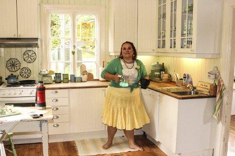 1 STILFULLT: Trine Lise elsker gamle farger. Kjøkkenbordet er arvegods. Kjøkkenet er fra Ikea og matcher de gamle vinduene og dørene. 2 HUSMANNSPLASS: Bygget rundt 1920 ifølge skjøtet. 3 SVARTOVN: Den er av gammel dato og en pryd. 4 FIGGJO: Trine Lise er en ivrig samler. 5 PINNESTOLER: Hun fant dem på loppemarked. Stolene og bordet hun har arvet, er malt i hennes lyse yndlingsfarger.  6 LOPPEMARKED: Trine Lise og hele familien hennes valfarter til loppemarkeder etter klenodier. 7 KUNSTNER: Til daglig jobber Trine Lise Feldmann som faciolog på Brilleland på Buskerud Storsenter. På fritida lager hun logoer og skilt, og får bestillinger fra hele Norge. Drømmen på sikt er å leve av dette. 8 KJÆRT ARVEGODS: Kommoden har hun arvet etter oldemor.