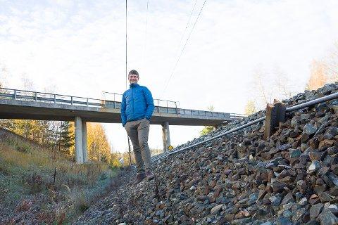 HÅPER: Audun Mjøs i Modum kommune håper de får grønt lys fra Bane NOR og Statens vegvesen til å lage gangvei langs jernbanen, under veibrua i bakgrunnen og bort til Øya.