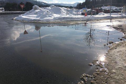 SPERRER: Denne vanndammen dekker hele innkjøringen mot Coop og Modumbygg i Vikersund, og gjør det vanskelig for gående å komme fram mellom snøhauger, biler og byggegjerder.