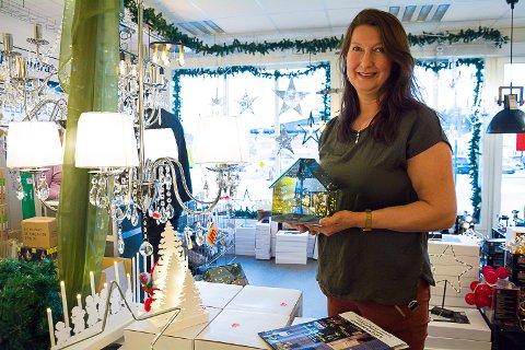 HØYSESONG: Inga-Lill Flattum i lampebutikken i Åmot har travle dager når folk skal pynte med lys til jul.. – Dette lyshuset med LED-lys inni er helt nydelig, sier hun.