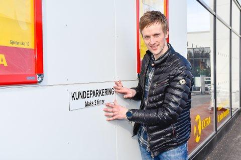 KORTTIDSPARKERING: Steffen Andersen henger opp nye skilter utenfor Vikersund Nærsenter.