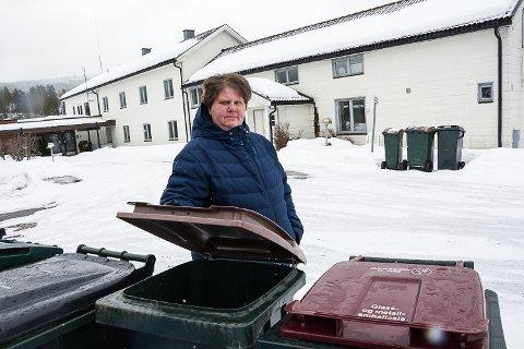 LEI: Anne Grete Mogen er lei av at beboerne på Sevalstunet kaster usortert søppel i og rundt hennes kildesorteringsdunker. Dunkene til Sevalstunet ses i bakgrunnen.