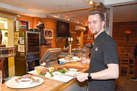 SERVICE:  Servitør Petter Holm har stadig et smil på lur når han serverer gjestene.
