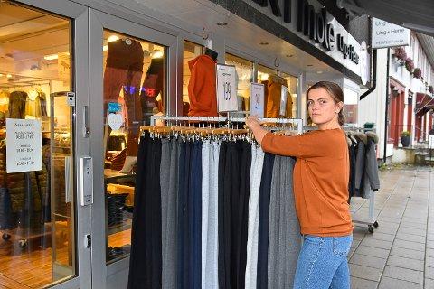 REDDER KLÆRNE: Når det regner løper butikkmedarbeider Nina Hoff ut for å ta inn klærne så de ikke skal bli sprutet ned.