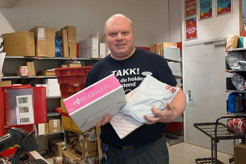 HENT RASKT: – Hent pakkene så fort du får melding, oppfordrer Thomas Hovde Marthinsen på Extra i Vikersund. Det vi ser i lokalet bak ham er bare en liten del av pakkene - på bakrommet har de ytterligere fem hyller og to containere.