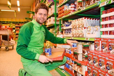 FYLLER OPP HERMETIKK: Butikksjef Lennart Lindberg fyller stadig opp med nye varer i hermetikkhyllene, men ser ingen grunn til at kunder skal hamstre varer på grunn av korona.