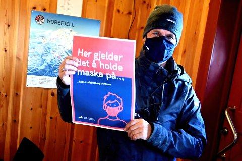 PLAKATER: Resortsjef Marius Arnesen på Norefjell gleder seg til han kan legge bort smittevernplakatene - forhåpentligvis for godt.