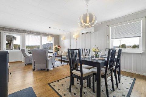 LYST OG TRIVELIG: Stue og spisestue i åpen løsning. Lyse farger og store vinduer gir et lyst og trivelig rom.