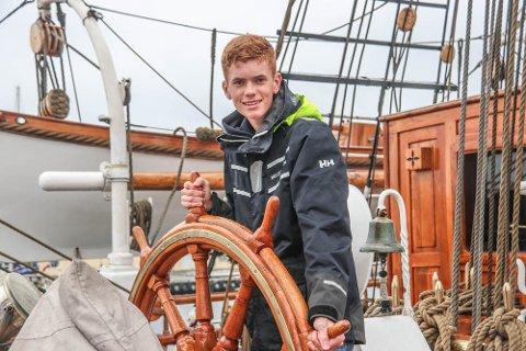 """Simen Sønstabø (16) fra Bjerkreim føler seg hjemme bak roret på """"Christian Radich"""". - Du får alltid nye utfordringer på sjøen, slår han fast."""