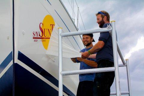 SUNTRIP: Anders Nakkerud og Andreas Dischler drar av folien over logoen på båten. (FOTO: PRIVAT)