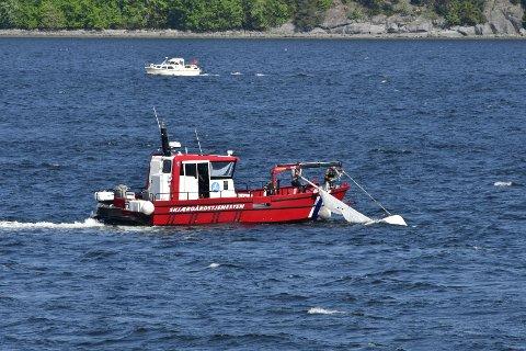 Reddet: En seiler ble reddet opp av vannet etter at båten kantret i Sandebukta søndag.