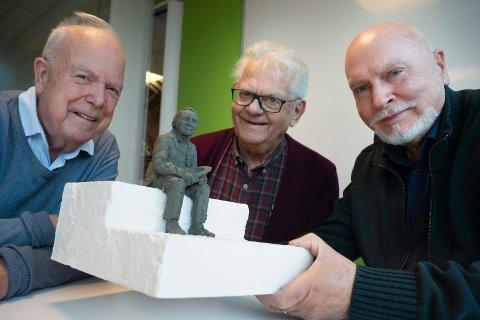 PÅ BENKEN: Miniatyr-utgaven som kunstner Merethe Bødtker har laget er slik de husker Sanger-Hans. Nå håper f.v. Nils Johan Rønniksen, Svein Winge og Vidar Fjeldstad at næringslivsaktører vil bidra til at en statue av Sanger-Hans kan realiseres.
