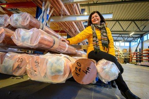 GLAD I METALL: Mette Borge Lindberg er daglig leder i Metallhuset Bergsøe AS - og Drammens tredje rikeste kvinne målt ut fra inntekt. Her sitter hun oppå en solid mengde kobberrør på firmaet lager på Lierskogen. Råmetallprisen ligger på rundt 60 kroner.
