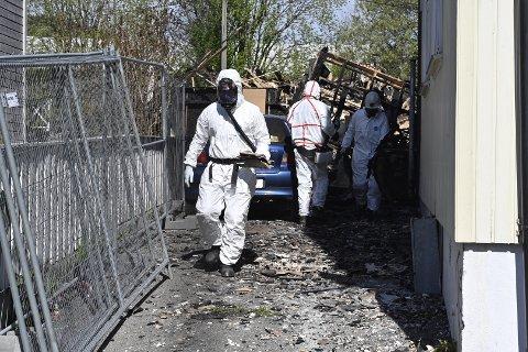 GASSMASKER: Iført gassmasker og hvite kjeledresser undersøkte Kripos tirsdag åstedet hvor to personer omkom i en brann natt til søndag.