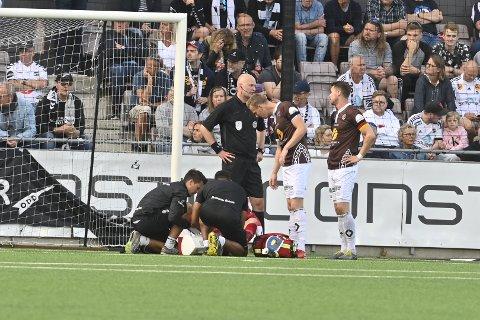 Her ligger Mjøndalen-keeper Julian Faye Lund nede etter å ha fått en vannflaske i leggen.