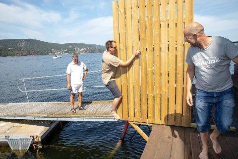 RISIKABELT: Håvard (klatrende) hadde ikke fått med seg at bryggen var stengt, men valgte likevel med en hjelpende hånd fra Vidar Jensen å klatre forbi stengselet. - Det er svært mange som ikke bryr seg om at det er satt opp vegger for å stenge av brygga, sier Jensen.