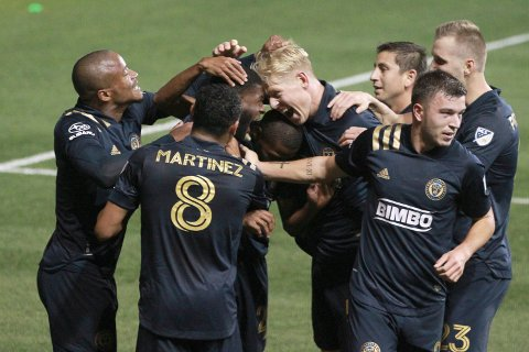 Mark McKenzie, left center, of the Philadelphia Union is mobbed by teammates including Jakob Glesnes, right center, after his goal against Toronto FC during the first half of an MLS match Saturday, Oct. 24, 2020, in Chester, Pa. (Charles Fox/The Philadelphia Inquirer via AP)
