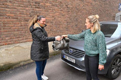 «DRIVE IN»-GARNBUTIKK: Ulla Garn & Broderi på Bragernes omsatte for mer enn noensinne i fjor, 9,6 millioner kroner. Kreative løsninger som dette, «drive in»-garnbutikk i korona-tida, bidro til det. Bildet ble tatt i mars, og viser Elisabeth Ottesen Pedersen (t.v.) som får varene hun har bestilt og betalt over Vipps overlevert av butikksjef Elin Bø.