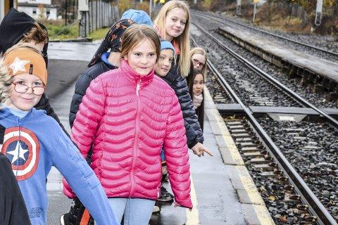 RESPEKT: Femte klasse ved Darbu skole peker på den gule linjen på perrongen, og forklarer at den er der for at vi skal holde oss godt bak den helt til toget står stille.