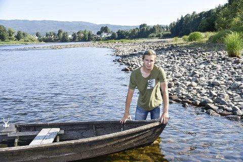 UNØDVENDIG: – Liten vits i å sette båten ut på elva nå. Laksen biter jo ikke, sier Stian Skjæreng. Her er lederen for aktivitetsutvalget i Østsiden Jeger- og Fiskerforening avbildet på Storsteinen ved Hellefoss.