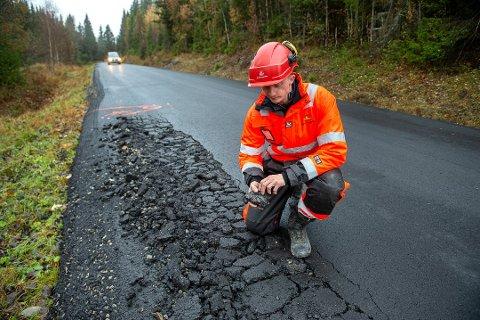 Bildet er fra oktober 2019. Byggeleder Vegar Antonsen befarer fylkesveg 162 og konstaterer at tungtrafikken smuldrer opp asfalten.