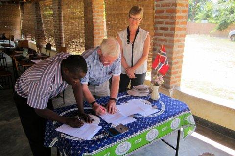 Ola Grønn Hagen og styreleiar i Kumudzi Kuwale signerer avtalen. Styreleiar i GHBMF Kari Bjørke til høgre i biletet.