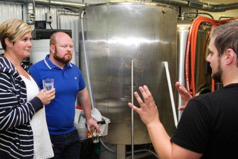Gareth og Mai er lutter øyre når Thomas Hovlandsvåg frå Kinn bryggeri fortel om prosessen som går føre seg i dei bakre regionane på Vesle Kinn. - Meininga er at vi skal eksperimentere litt her, og at vi kan lage ting du må innom lokala har for å få smake på, seier han.