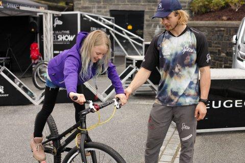 Andrine Steindal (10) frå Flora Cykleklubb testa trialsykkel med proffsykling Eirik Ulltang.