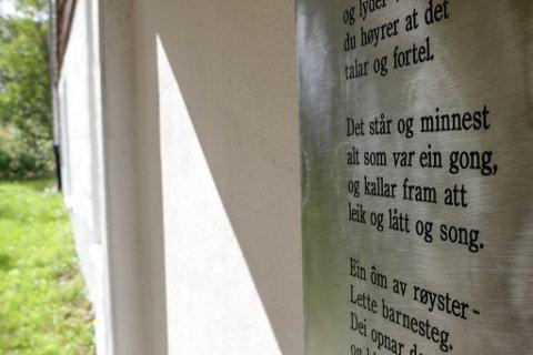 """Skulehuset: På baksida av skulehuset heng dette diktet. Eit av versa er """"Det står og minnast - alt som var ein gong, - og kallar fram att - leik og lått og song"""""""