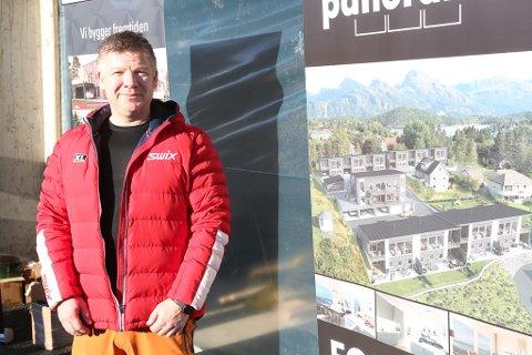 Rune Ottesen ved plakat som viser prosjektet sett frå lufta. Berre ei av dei bakerste rekkene er ikkje starta bygging på.